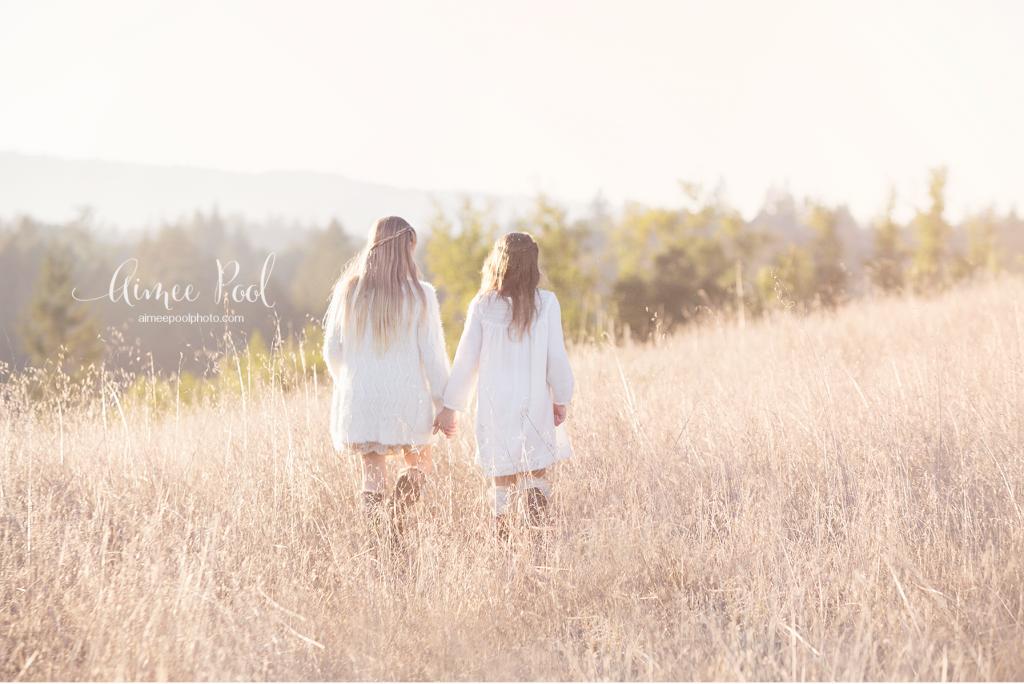 Sisters walking in field - www.aimeepoolphoto.com